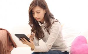 【生活】タブレットPCを使って治療院を予約する女性